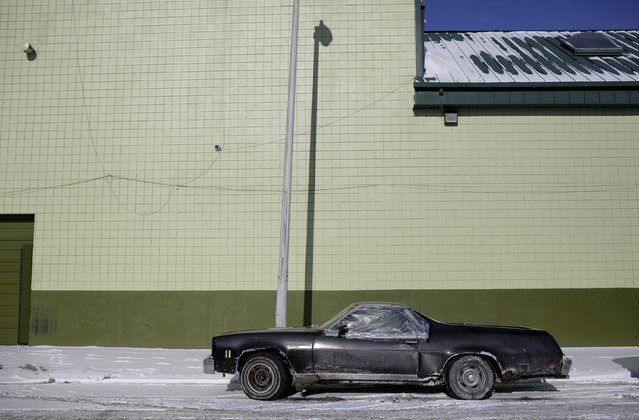 A Chevrolet El Camino with rust spots and a missing window sits parked outside of a building in Detroit, Michigan January 10, 2015. (Photo by Joshua Lott/Reuters)