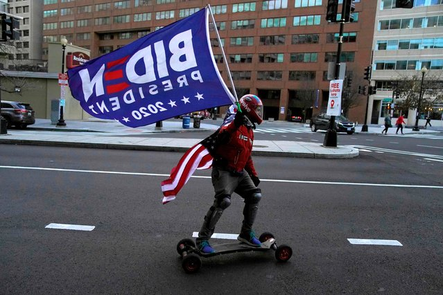 A skateboarder holds a Biden flag, with a US National falg tied to his neck, ahead of the inauguration ceremonies for President-elect Joe Biden and Vice President-elect Kamala Harris on January 18, 2021 in Washington, DC. President-elect Joe Biden and Vice President-elect Kamala Harris will be sworn into office January 20, 2021. (Photo by Timothy A. Clary/AFP Photo)