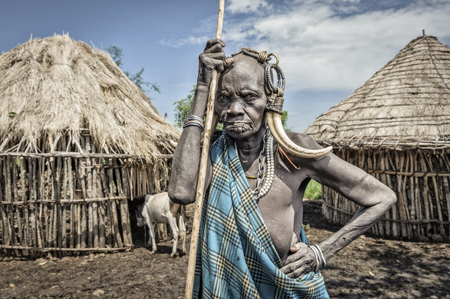 """Old Mursi woman"". Old woman by the huts of her village. Location: Marenke, Omo valley, Ethiopia. (Photo and caption by Jorge Fernandez/National Geographic Traveler Photo Contest)"