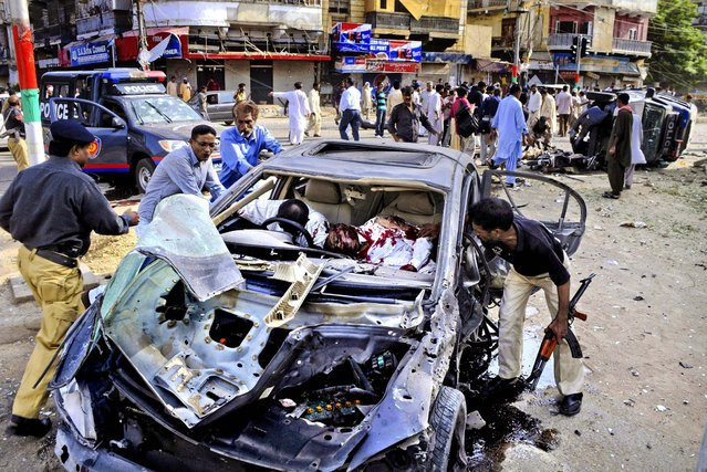 Police officers and civilians move the lifeless bodies of a driver and a policeman after a bomb blast in Karachi, Pakistan, on June 26, 2013. A bomb targeting a senior judge in Karachi wounded him and killed several security personnel. (Photo by Wasi Qureshi/Associated Press)