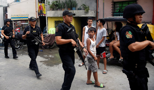 Members of Philippine National Police's SWAT team hold their weapons as they walk past residents during an anti-drugs operation in Mandaluyong, Metro Manila in the Philippines, November 10, 2016. (Photo by Erik De Castro/Reuters)