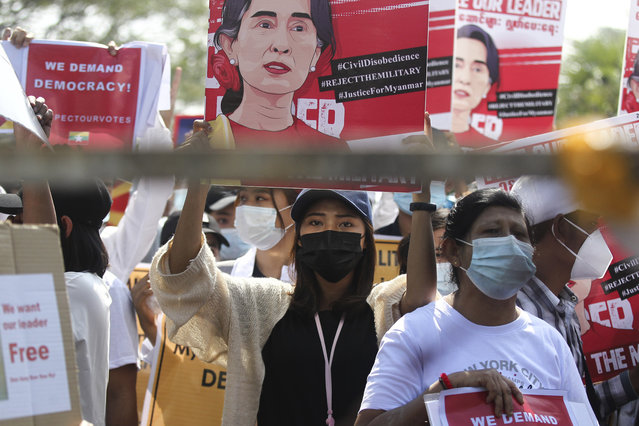 An anti-coup protester holds up a poster with an image of deposed Myanmar leader Aung San Suu Kyi during a rally outside the Central Bank of Myanmar building in Yangon, Myanmar on Monday, February 15, 2021. Myanmar's military leaders have extended their detention of Suu Kyi, whose remand was set to expire Monday and whose freedom is a key demand of the crowds of people continuing to protest this month's military coup. (Photo by AP Photo/Stringer)