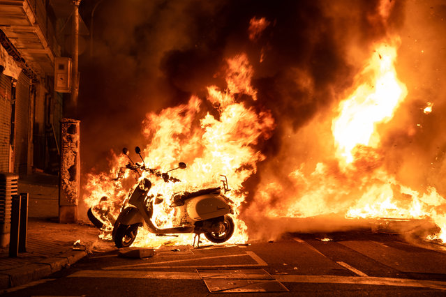 Burning motorcycles during another night of protests and riots in response to the arrest and imprisonment of rapper Pablo Hasél in Barcelona, Spain on February 17, 2021. The rapper has been accused of exalting terrorism and insulting the crown for the content of the lyrics of his songs. (Photo by Paco Freire/SOPA Images/Rex Features/Shutterstock)