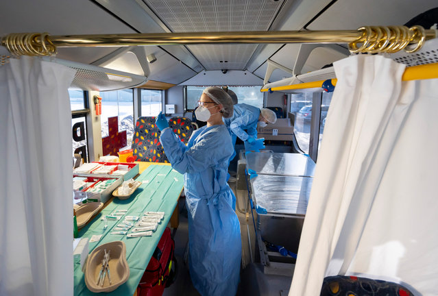 Nurses Annett Goebel and Bernadett Laub prepare doses of the Pfizer/BioNTech Comirnaty vaccine at a mobile vaccination center situated in a modified bus in Grosshartmannsdorf, Germany, February 21, 2021. The state of Saxony is testing several mobile vaccination units, including the converted bus as well as truck-pulled trailers, in an effort to better reach rural communities that might otherwise be far from one of the state's mass vaccination centers. (Photo by Matthias Rietschel/Getty Images)