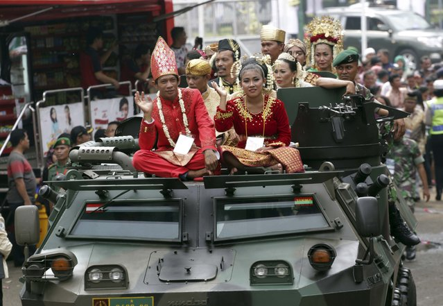 Brides and grooms sit on top of an Indonesian Army vehicle during a mass wedding ceremony organized in Jakarta, Indonesia, Wednesday, January 28, 2015. Thousands of couples registered for the mass marriage sponsored by the Indonesian Armed Forces. (Photo by Achmad Ibrahim/AP Photo)