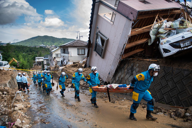 Police arrive to clear debris scattered on a street in a flood hit area in Kumano, Hiroshima prefecture on July 9, 2018. Rescue workers in Japan battled on July 9 to reach residents trapped after devastating rains that have killed at least 75 people, as authorities warned about the risk of landslides. (Photo by Martin Bureau/AFP Photo)