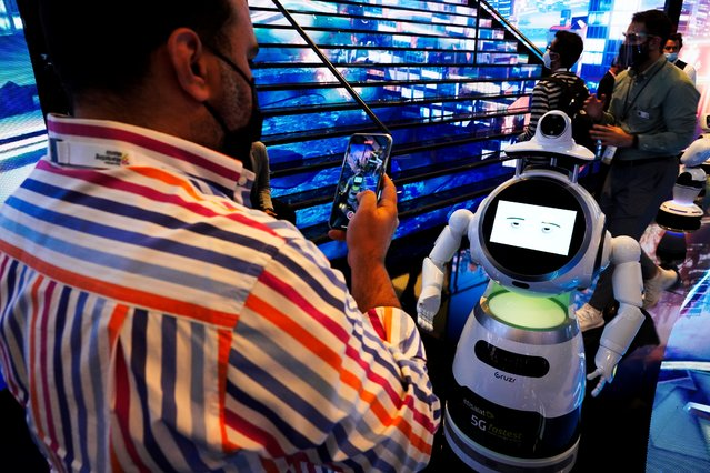 A man takes a video of a robot at the GITEX technology summit in Dubai, United Arab Emirates, Monday, December 7, 2020. As the coronavirus pandemic still causes smaller crowds than normal at Dubai events, this year's annual GITEX summit got a boost from Israelis who traveled to the UAE for the event after the recent normalization deal between the two countries. (Photo by Jon Gambrell/AP Photo)
