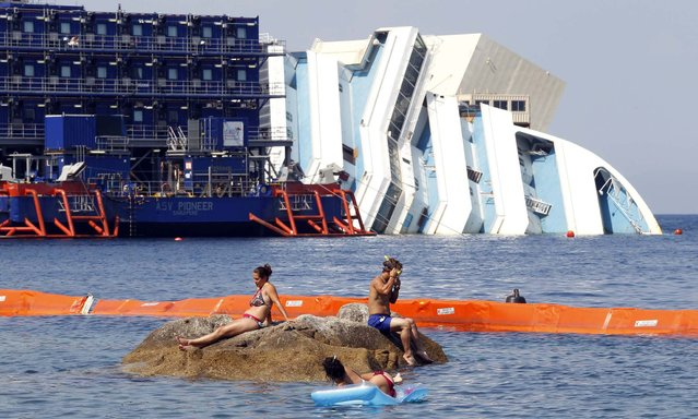 People sunbathe in front of the capsized cruise liner Costa Concordia lying surrounded by cranes outside Giglio harbour July 17, 2013. The trial of the captain of the Costa Concordia cruise ship, which capsized off Italy's coast last year killing 32 people, resumes on Wednesday after it was delayed by a lawyers' strike earlier this month. The trial will examine one of the most dramatic marine accidents in recent Italian history, when the huge liner struck a rock outside the port of Giglio in January 2012 and keeled over on to its side, setting off a chaotic night-time evacuation of more than 4,000 passengers and crew. Schettino, accused of abandoning ship before all crew and passengers had been rescued, faces charges including manslaughter and causing the loss of his ship, which still rests on its side in the Tuscan port. (Photo by Giampiero Sposito/Reuters)