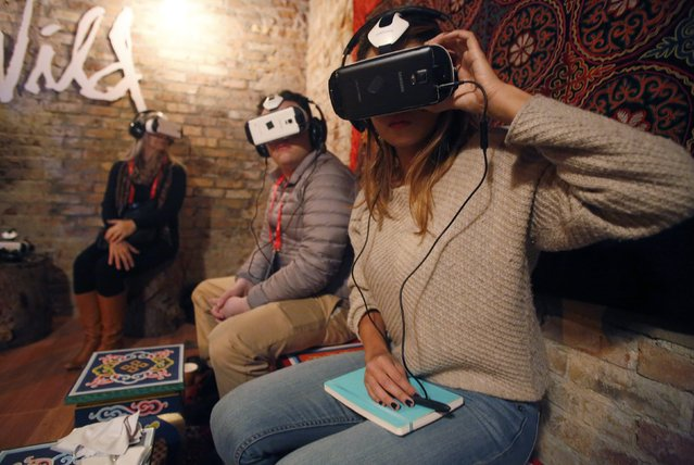 Members of the media try earphones and a headset used for virtual reality  at the Sundance Film Festival in Park City, Utah January 23, 2015. The content is viewed on a wraparound-style headset that project a 360-degree panorama, giving viewers the feel of being in the action. (Photo by Jim Urquhart/Reuters)