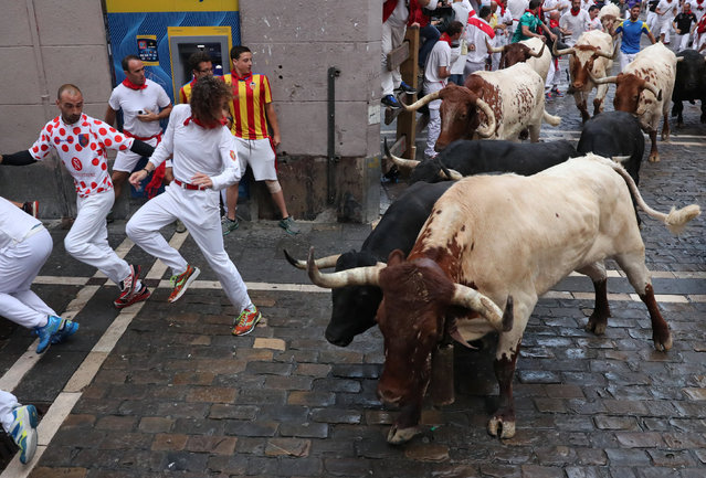 Revellers sprint in front of bulls during the sixth running of the bulls of the San Fermin festival in Pamplona, Spain, July 12, 2018. (Photo by Susana Vera/Reuters)
