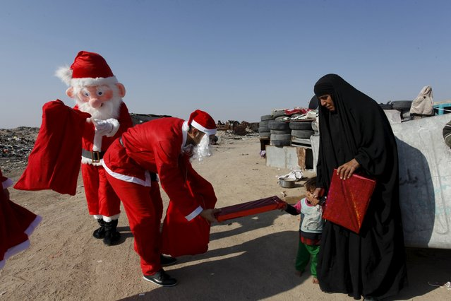 Volunteers wearing Santa Claus costumes distribute presents to children at a poor community in Najaf, south of Baghdad, December 19, 2015. (Photo by Alaa Al-Marjani/Reuters)
