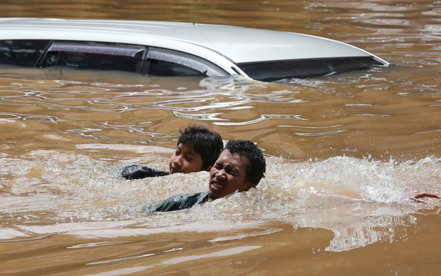 People swim through a flooded neighborhood following heavy rains in Jakarta, Indonesia, Saturday, February 20, 2021. Heavy downpours combined with poor city sewage planning often causes heavy flooding in parts of greater Jakarta. (Photo by Tatan Syuflana/AP Photo)