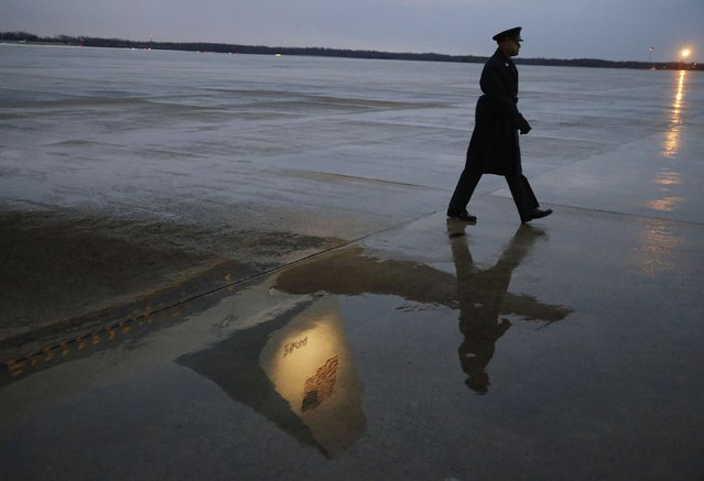 The tail section of Air Force One is reflected in the wet pavement as a USAF Security Forces member walks to his position before U.S. President Barack Obama arrives at Andrews Air Force Base outside Washington, January 29, 2015. Obama is departing for Philadelphia and is scheduled to return later this evening. (Photo by Larry Downing/Reuters)