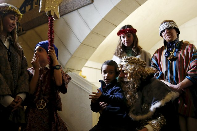 A boy sits on the lap of a volunteer dressed as one of the Three Wise Men during a distribution of free toys for low-income families at Almudena Cathedral in Madrid, Spain, December 22, 2015. (Photo by Susana Vera/Reuters)