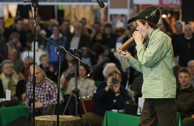 "Nils, 12, uses a specially designed instrument at the German championships in Deer-Calling at the ""Jagd & Hund"" exhibition in Dortmund February 6, 2015. (Photo by Ina Fassbender/Reuters)"