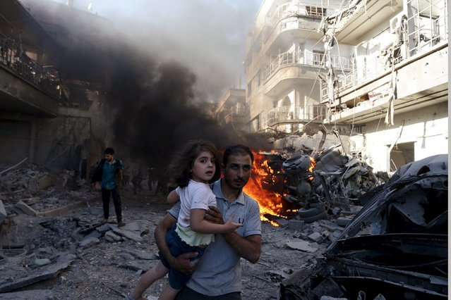 A man carries a girl as they rush away from a site hit by what activists said were airstrikes by forces loyal to Syria's President Bashar al-Assad in the Douma neighbourhood of Damascus, Syria August 24, 2015. (Photo by Bassam Khabieh/Reuters)