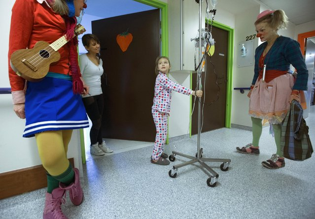 Malena, 7, looks at Belgian clowns Jupette (L) and Lili Bellule at the pediatric department of the Hopital Erasme at the Universite Libre de Bruxelles (ULB), in Brussels January 27, 2015. (Photo by Yves Herman/Reuters)