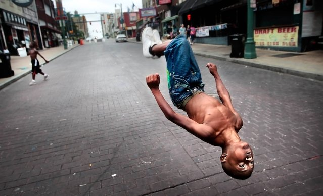 Beale St. Flipper Markese Jones, 10, spins head-over-heels down the famed street in Memphis, Tenn. as Marcus Houston, left, picks up donations from tourists Sunday, August 25, 2013. (Photo by Jim Weber/AP Photo/The Commercial Appeal)