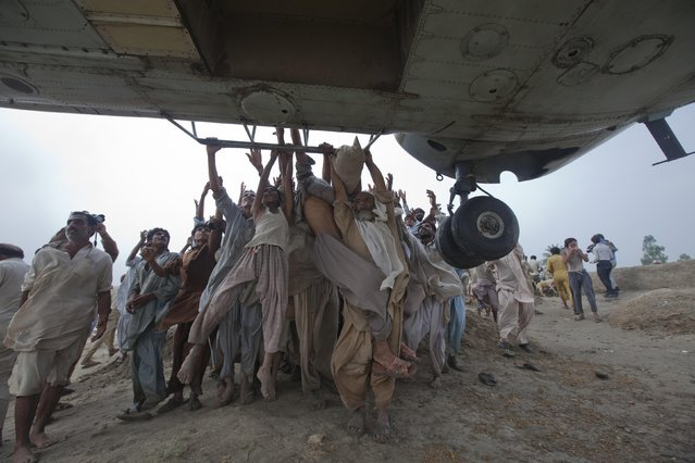 Marooned flood victims try to grab onto the side bars of a hovering army helicopter which arrived to distribute food supplies in the Muzaffargarh district of Pakistan's Punjab province in this August 7, 2010 file photo. Pakistanis desperate to get out of flooded villages threw themselves at helicopters as more heavy rain was expected to intensify both suffering and anger with the government. The disaster killed more than 1,600 people and disrupted the lives of 12 million. (Photo by Adrees Latif/Reuters)
