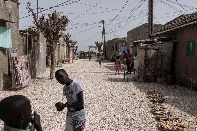 Children play along a road of clam shells in the Island of Fadiouth, Senegal on April 3, 2021. (Photo by John Wessels/AFP Photo)