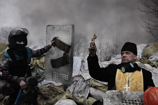 Jerome Sessini, a French photographer of Magnum Photos on assignment for the De Standaard, won the Second Prize in the Spot News Category, Stories, of the 2015 World Press Photo contest with his series of pictures which includes this one of a protester calling for medical aid for a comrade shot dead in Kiev, taken February 20, 2014 and released by the World Press Photo on February 12, 2015. (Photo by Jerome Sessini/Reuters/Magnum Photos/World Press Photo)