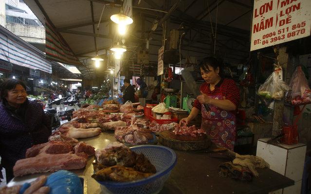 A pork seller (R) chops bones for sale at a market in Hanoi, Vietnam December 24, 2015. (Photo by Reuters/Kham)