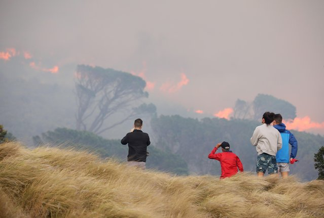 Residents look on as fires fanned by strong winds engulf the slopes of Table Mountain in Cape Town, South Africa, April 19, 2021. (Photo by Mike Hutchings/Reuters)