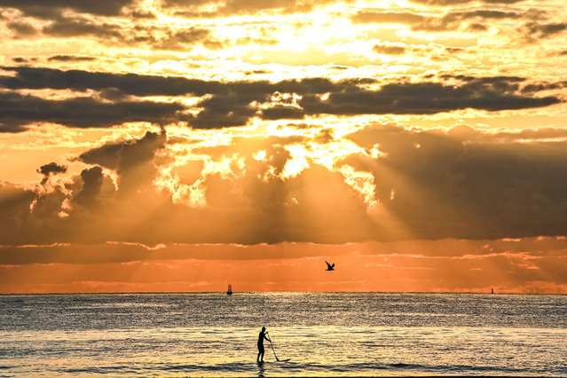 A man paddleboards during a sunrise on the beach in Miami Beach, Florida, on March 23, 2021. (Photo by Chandan Khanna/AFP Photo)