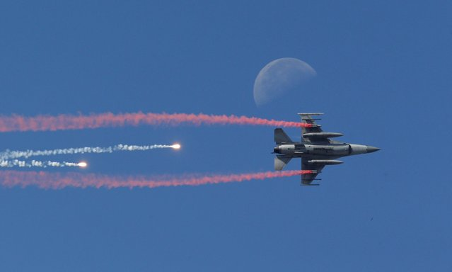 A South Korean Air Force F-16 fighter jet fires flare shells past the moon during the media day for the 65th anniversary of Armed Forces Day at Seoul military airport in Seongnam, South Korea, Friday, September 27, 2013. South Korean Armed Forces was found in 1948 and Armed Forces Day is observed on October 1, the day that South Korean forces broke through the 38th parallel in 1950 during the Korean War. (Photo by Lee Jin-man/AP Photo)