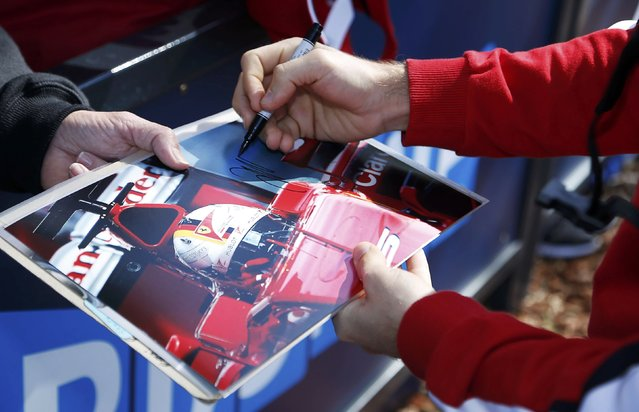 Ferrari Formula One driver Sebastian Vettel of Germany (R) signs autographs as he arrives for the first practice session of the Australian F1 Grand Prix at the Albert Park circuit in Melbourne March 13, 2015.    REUTERS/Brandon Malone