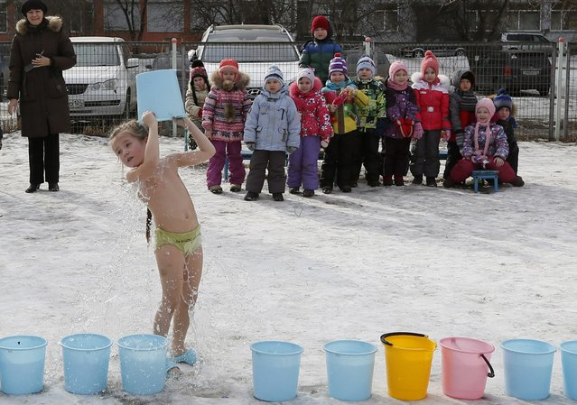 Children watch their classmate pour cold water on herself under the watch of a fitness coach at a local kindergarten in Russia's Siberian city of Krasnoyarsk, March 11, 2015. The program, which also involves sports training and sauna usage, has been practiced by the kindergarten for more than 15 years as they believe it has health benefits and keeps the children fit. (Photo by Ilya Naymushin/Reuters)
