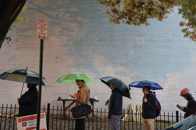 Voters line up in the rain outside Bright Family and Youth Center in the Columbia Heights neighborhood in Washington, Tuesday, November 6, 2018. Across the country, voters headed to the polls Tuesday in one of the most high-profile midterm elections in years. (Photo by Pablo Martinez Monsivais/AP Photo)