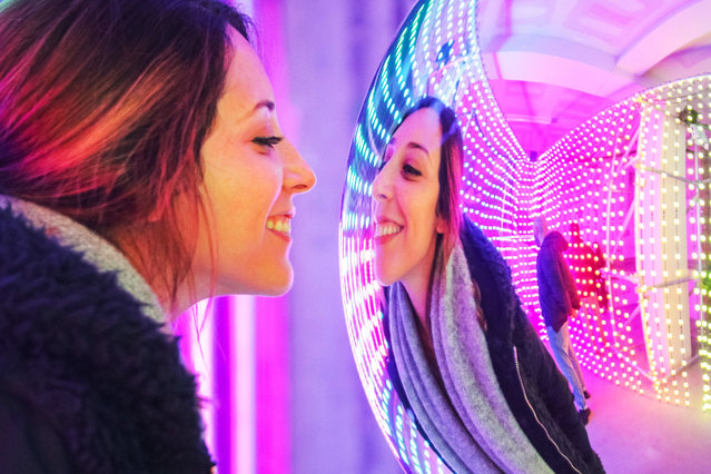 A visitor is reflected in a light installation at Mulberry Lights on Regent Street in London, UK on November 16, 2018. Visitors have fun taking selfies and posing with the colourful light installations. Mulberry Lights is a series of illuminating interactive experiences that celebrate how light, colour, shapes and people come together to create a modern British Christmas. It runs at 100 Regent Street until November 18, The London pop-up is the start of a nationwide campaign with further installations to follow. (Photo by Imageplotter/Rex Features/Shutterstock)
