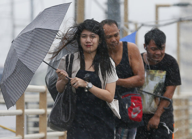 People brave the rain and wind brought about by typhoon Nock-Ten, a day after Christmas Monday, December 26, 2016 at suburban Paranaque city southeast of Manila, Philippines. (Photo by Aaron Favila/AP Photo)