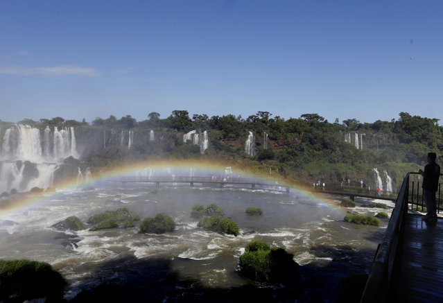 In this March 15, 2015 photo, a rainbow arches over the water at Iguazu Falls in Brazil. From above, the Iguazu Falls resemble a massive hole in a river surrounded by thick jungle. (Photo by Jorge Saenz/AP Photo)