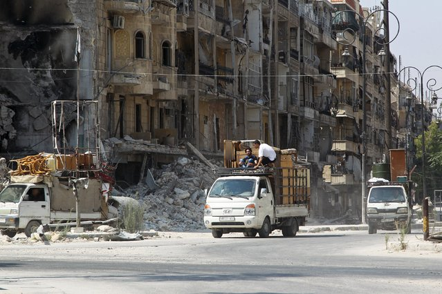 Men drive pick-up trucks past damaged buildings as they transport furniture in the old city of Aleppo, Syria August 24, 2015. (Photo by Abdalrhman Ismail/Reuters)