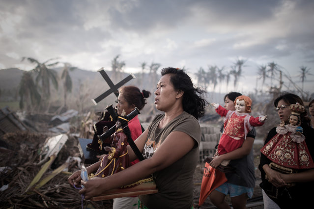 Survivors of Super Typhoon Haiyan march during a religious procession in Tolosa on the eastern Philippine island of Leyte on November 18, 2013 over one week after Super Typhoon Haiyan devastated the area.  The United Nations estimates that 13 million people were affected by Super Typhoon Haiyan with around 1.9 million losing their homes. (Photo by Philippe Lopez/AFP Photo)