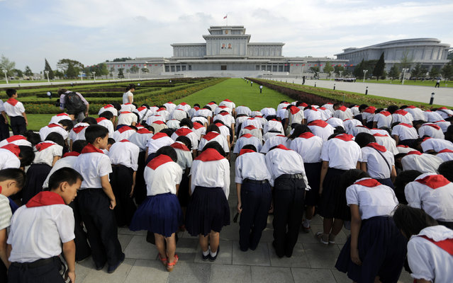 North Korean students bow in front of Kumsusan Palace of the Sun, where the embalmed bodies of North Korea's founding leader Kim Il-sung and his son Kim Jong-il lie in state, in Pyongyang July 25, 2013. (Photo by Jason Lee/Reuters)