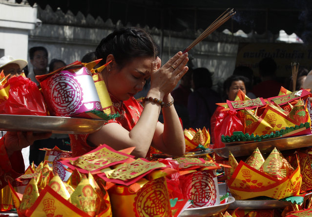 A woman prays at a temple to celebrate Chinese New Year in Nonthaburi province, on the outskirts of Bangkok, Thailand February 8, 2016. (Photo by Chaiwat Subprasom/Reuters)