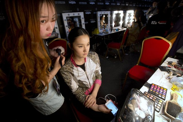A model and stylist look in a mirror as they apply makeup backstage while preparing to present creations by Chinese designer Zeng Fengfei during China Fashion Week in Beijing, Sunday, March 29, 2015. (Photo by Mark Schiefelbein/AP Photo)