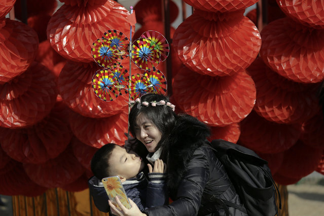 A boy kisses a woman taking pictures in front of decoration at the Longtan park as the Chinese Lunar New Year, which welcomes the Year of the Monkey, is celebrated in Beijing, China February 9, 2016. (Photo by Damir Sagolj/Reuters)