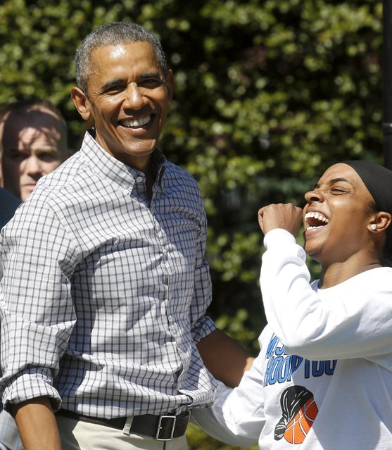 U.S. President Barack Obama reacts while playing basketball with Bilqis Abdul-Qaadir (R) as he takes a tour of the exercise activities at the annual Easter Egg Roll at the White House in Washington April 6, 2015. (Photo by Jonathan Ernst/Reuters)