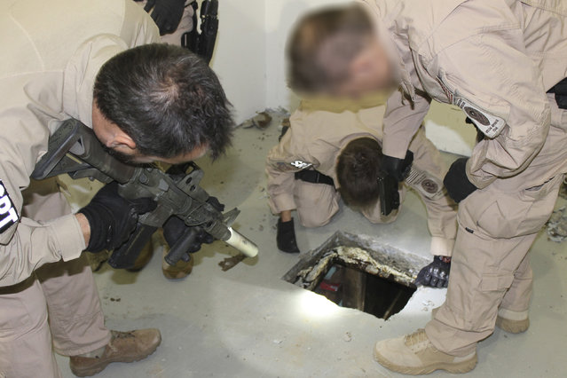 Law enforcement officers inspect a drug tunnel found in a warehouse in Otay Mesa, California, April 3, 2014. U.S. federal agents uncovered two drug-smuggling tunnels underneath the U.S.-Mexico border, both surfacing in San Diego-area warehouses and equipped with rail systems for moving contraband. The discovery led to the arrest of a 73-year-old woman accused of running one of the warehouses connected to a drug smuggling operation. (Photo by Reuters/Immigration and Customs Enforcement)