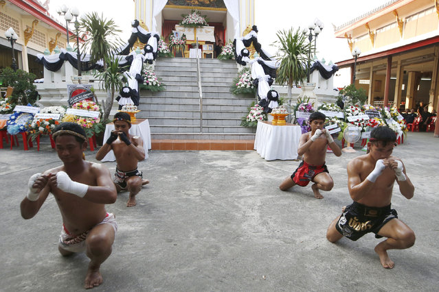 In this Thursday, November 15, 2018, photo, Thai boxers perform their traditional dance showing respect at the coffin of 13-year-old Thai kickboxer Anucha Tasako during his funeral services in Samut Prakan province, Thailand. Anucha died of a brain hemorrhage two days after he was knocked out in a bout on Nov. 10 that was his 174th match in the career he started at age 8. Thai lawmakers recently suggested barring children younger than 12 from competitive boxing, but boxing enthusiasts strongly oppose the change. (Photo by Sakchai Lalit/AP Photo)