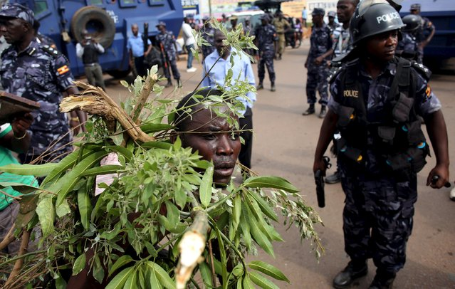 An opposition supporter walks in front of policemen in Kampala, Uganda February 15, 2016. (Photo by Goran Tomasevic/Reuters)