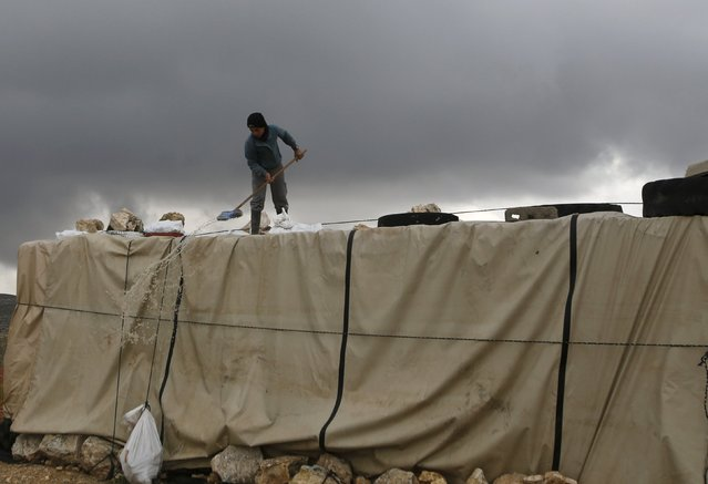 A Palestinian removes rainwater from a tent during snow storm in West Bank Village of Mufagara, south of Hebron January 27, 2016. (Photo by Mussa Qawasma/Reuters)