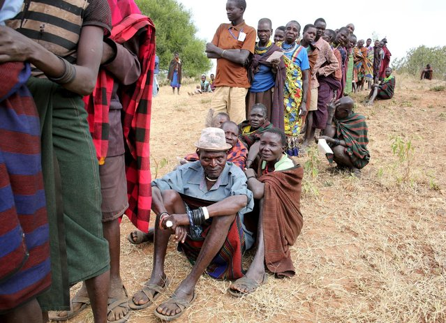 People from Karamojong tribe wait in line to vote at a polling station during the presidential elections in a village near town of Kaabong in Karamoja region, Uganda, February 18, 2016. (Photo by Goran Tomasevic/Reuters)