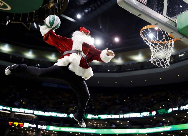 A performer makes a trick dunk during a timeout in the fourth quarter of a game between the Boston Celtics and the Minnesota Timberwolves in Boston on December 16, 2013. (Photo by Michael Dwyer/Associated Press)