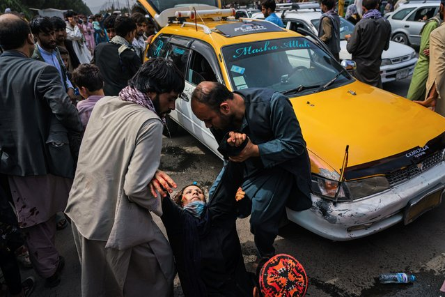 Men try to help a wounded woman and her wounded child after Taliban fighters use guns fire, whips, sticks and sharp objects to maintain crowd control over thousands of Afghans who continue to wait outside the Kabul Airport for a way out, on airport road in Kabul, Afghanistan, Tuesday, August 17, 2021. (Photo by /Marcus Yam/Los Angeles Times/Rex Features/Shutterstock)