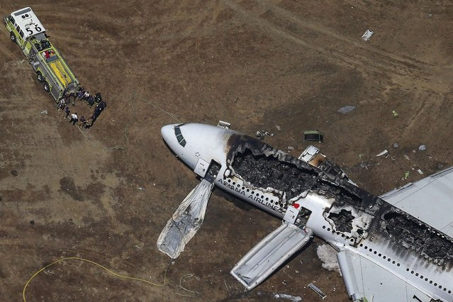 Rescue officials stand near an Asiana Airlines Boeing 777 plane after it crashed while landing at San Francisco International Airport in California July 6, 2013. (Photo by Jed Jacobsohn/Reuters)